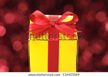 Gold gift on red blurry lights background. - stock photo