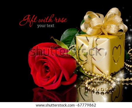 Gold gift with red rose on black background. Copy-space
