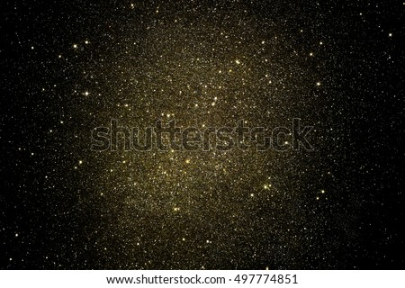 Gold glitter on black background. Golden abstract grainy  texture  with bright center. Christmas, holiday, festive backdrop.