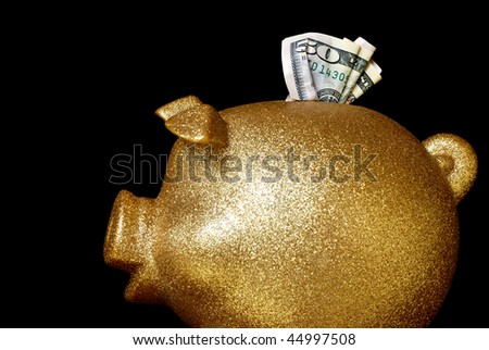 Gold glitter piggy bank with $50 isolated on black background.  Macro with sharpest focus on the cash.  Copy space included.