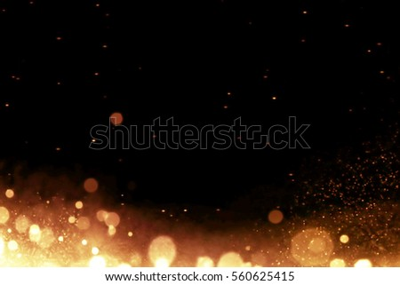 gold glow particles bokeh flowing effect on black background, holiday happy new year concept #560625415