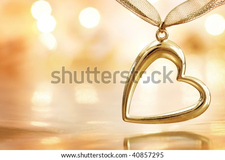 Gold heart pendant hanging over golden reflective background with defocused lights. Shallow DOF.