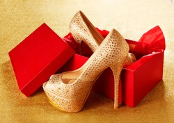 Gold high heels with red shoes box. on the golden paper background. Christmas present, Valentine gift. Shopping