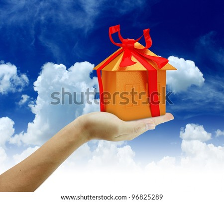Gold home in hand with blue sky background. - Shutterstock ID 96825289