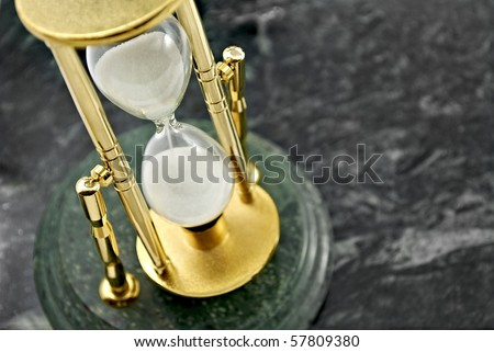 Gold hourglass on a marble background