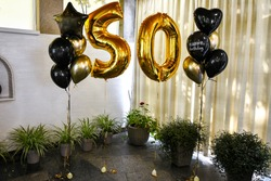 Gold inflatable balls in the form of a figure 50, Birthday anniversary party. Gold 50th Birthday Party Balloons. Photoshooting zone