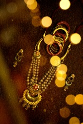 gold jewellery golden necklace(haar) bracelets butti dark background with bokeh bride getting ready for beauty parlour beautiful ornaments