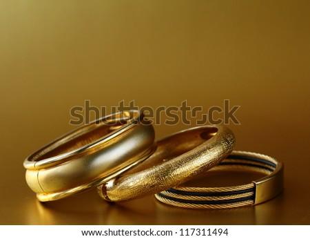 gold jewelry, bracelets  on gold background