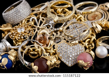 Gold jewelry on a black background - stock photo