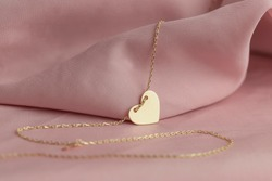 Gold jewelry on a pink background. Gift for Valentine's Day. Pleasure girlfriends, women, wives. Preparing for Valentine's Day. Pure pink background, fabric. earrings, ring, diamonds, chain