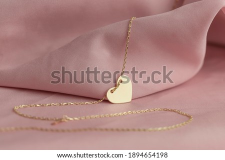 Gold jewelry on a pink background. Gift for Valentine's Day. Pleasure girlfriends, women, wives. Preparing for Valentine's Day. Pure pink background, fabric. earrings, ring, diamonds, chain Photo stock ©
