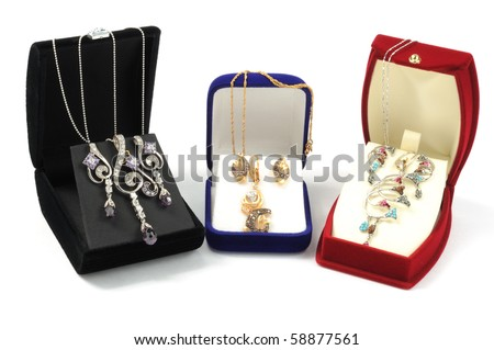 Gold jewelry sets in open boxes, on white background