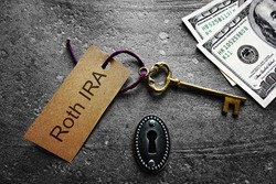 Gold key with Roth IRA tag, with keyhole and cash
