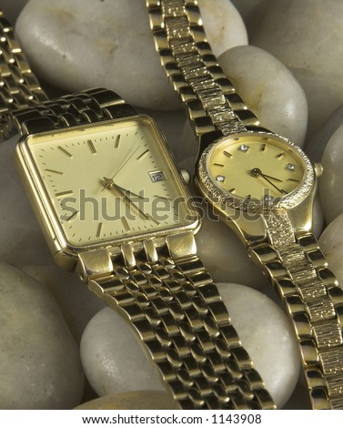 Gold ladies and mens watches on white pebble background