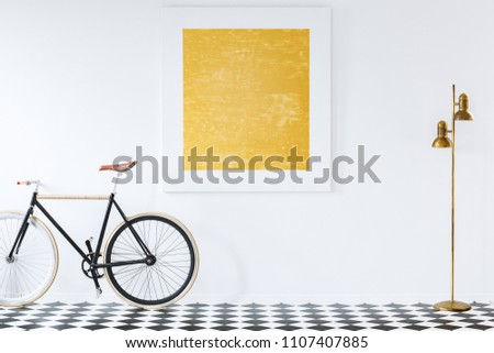 Gold lamp and black bike on checkerboard floor in anteroom interior with painting on the wall