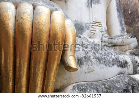 gold leaf covered slender fingers of big buddha staute in wat si chum in the sukhothai historic park in northern thailand