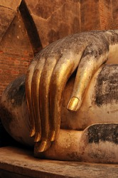 gold leaf offerings on slender fingers of wat si chums iconic big buddha statue in sukhothai historic park northern thailand