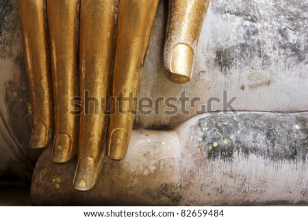gold leaf offerings on slender fingers of wat si chums iconic big buddha statue in sukhothai historic park northern thailand #82659484