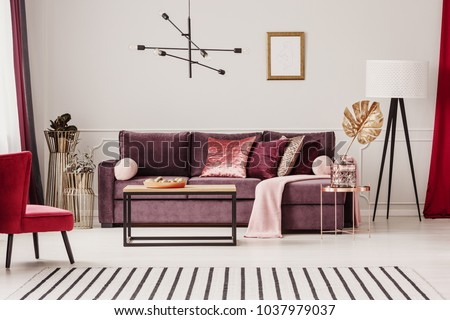 Gold leaf on copper table in sophisticated living room interior with striped carpet and violet sofa #1037979037