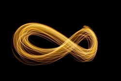 Gold light painting photography - infinity loop shape curves and waves of metallic yellow light against a black background