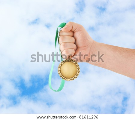 Gold medal in hand on sky background