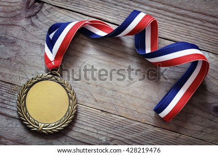 Gold medal on wood background with blank face for text, concept for winning or success