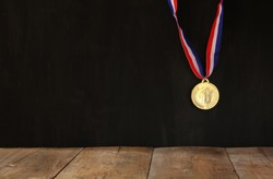Gold medal over textured black background with room for text, winning and success concept