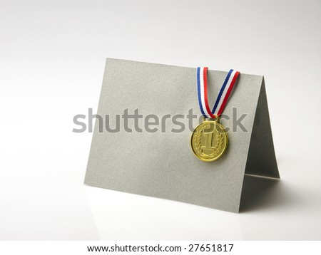 gold medal rest on a gray color greeting card