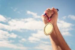 Gold medal winner held in hand raised against blue sky background