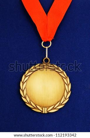 Gold medal with red ribbon on blue velveteen