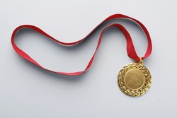 Gold medal with space for design on light background, top view. Victory concept