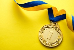 Gold medallion for the winner or champion in a competition or race on a blue and yellow twirled ribbon over a matching yellow background with copyspace