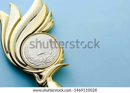 Gold medallion winners trophy with laurel wreath for the winner of a competition of championship event over grey with copy space #1469110028