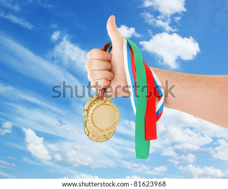 Gold medals in hand on sky background