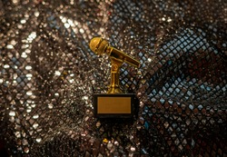 Gold, metallic microphone, mike, mic statuette, figurine medal award for musical achievement with place for title and text of winner on isolated bokeh shiny beaded gold background