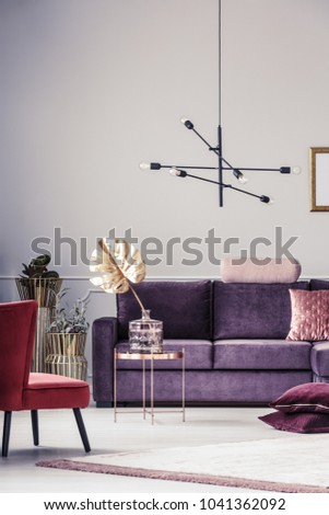 Gold monstera leaf on a copper table near red armchair, pillows and violet sofa in cozy living room interior