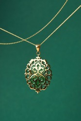 Gold necklace on green background. Jewelry chain with gold pendant. Luxury female jewelry