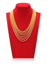 Gold necklace on necklace display stand. Red mannequin.