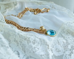 Gold necklace with aquamarine on white cloth
