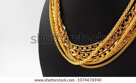 Stock Photo Gold necklaces on necklace display stand.