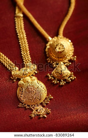 Gold Necklaces on textured cloth background.