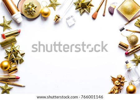 gold New Year's cosmetics for a present to luxury beautiful ladies around golden balls and stars, new year`s decorations on the white background  #766001146