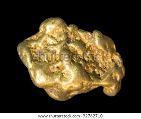 Gold nugget isolated on black. This is real.
