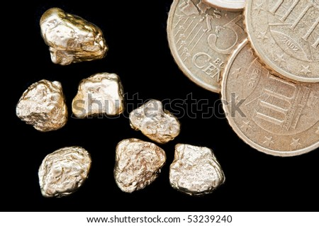 Gold nuggets and money, euro coins on a black background. closeup.