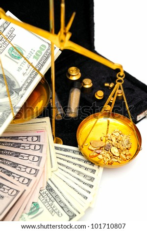 Gold nuggets in the pan of a balance scale with many fifty and hundred dollar bills showing the value of both