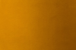 Gold or yellow paint on cement wall texture as background