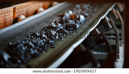 Gold ore mining and processing. Concentrating plant. Conveyor belt with gold ore rocks. Low depth-of-field. Focus on center stones. Foto d'archivio ©