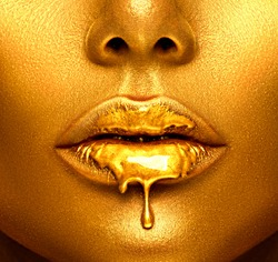 Gold Paint drips from the lips, lipgloss dripping from sexy lips, golden liquid drops on beautiful model girl's mouth, gold metallic skin make-up. Beauty woman face makeup close up.