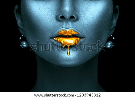 Gold Paint drips from the lips, lipgloss dripping from sexy lips, golden liquid drops on beautiful model girl's mouth, creative abstract dark blue skin make-up. Beauty woman face makeup close up.