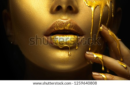 Gold Paint smudges drips from the face lips and hand, lipgloss dripping from sexy lips, golden liquid drops on beautiful model girl's mouth, gold metallic skin make-up. Beauty woman makeup close up.